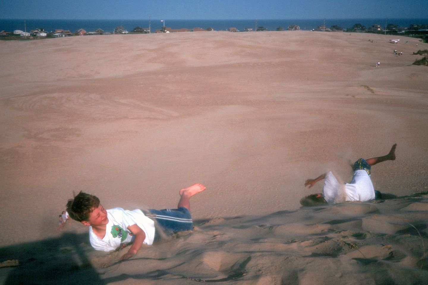 Boys rolling down the Jocky Ridge dune
