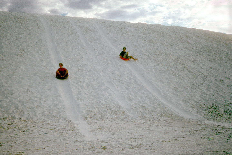Boys saucering down dunes
