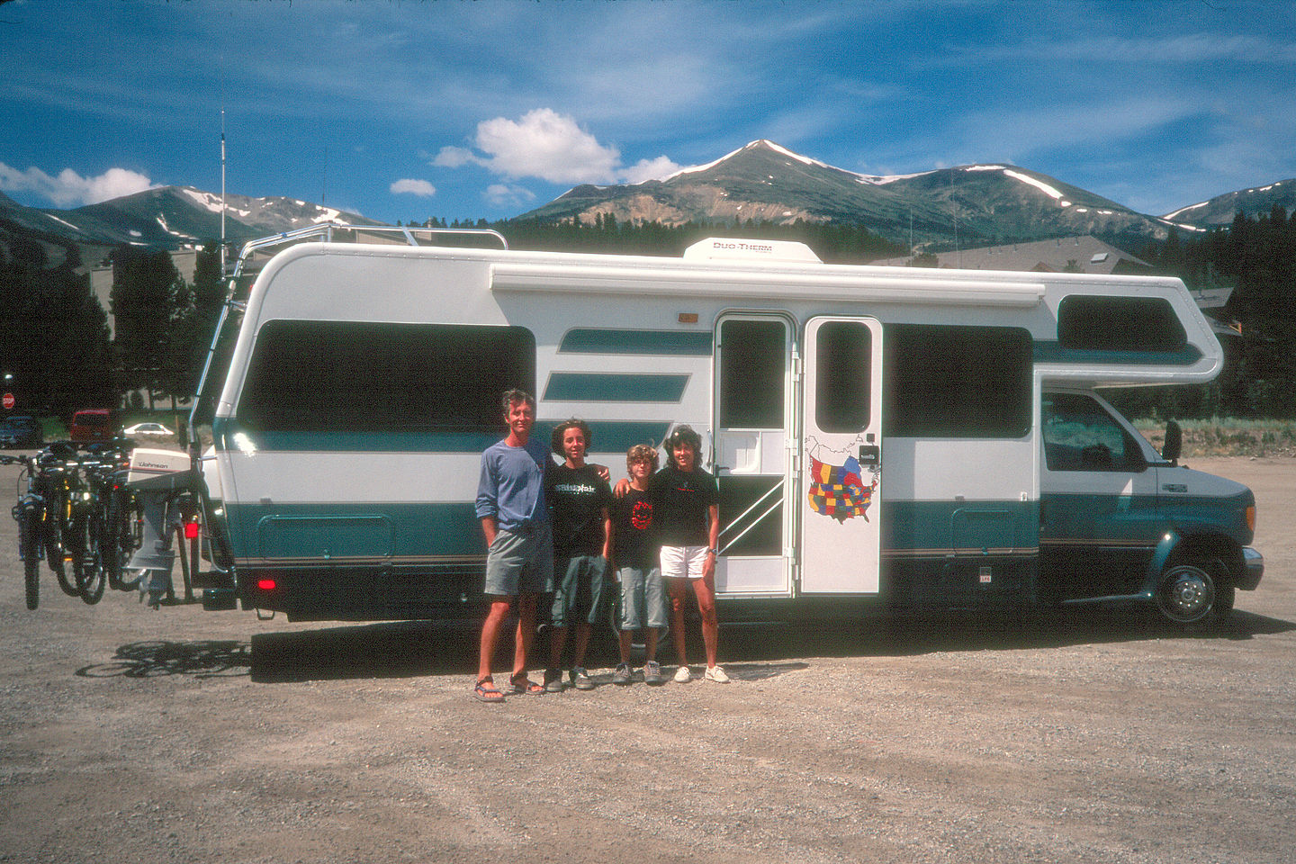 Family RV shot with snowcapped mountains
