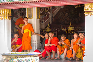 Young Buddhist monks playing with their material possessions