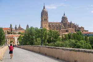 Lolo walking across the Roman Bridge towards the Salamanca Cathedral