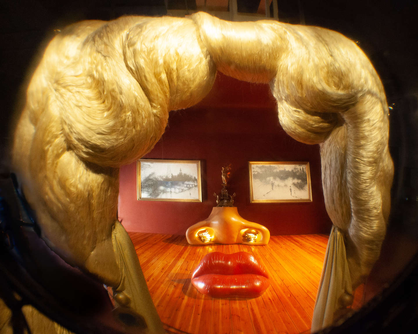 Mae West room with sofa lips, a fireplace nose, and two paintings for her eyes.