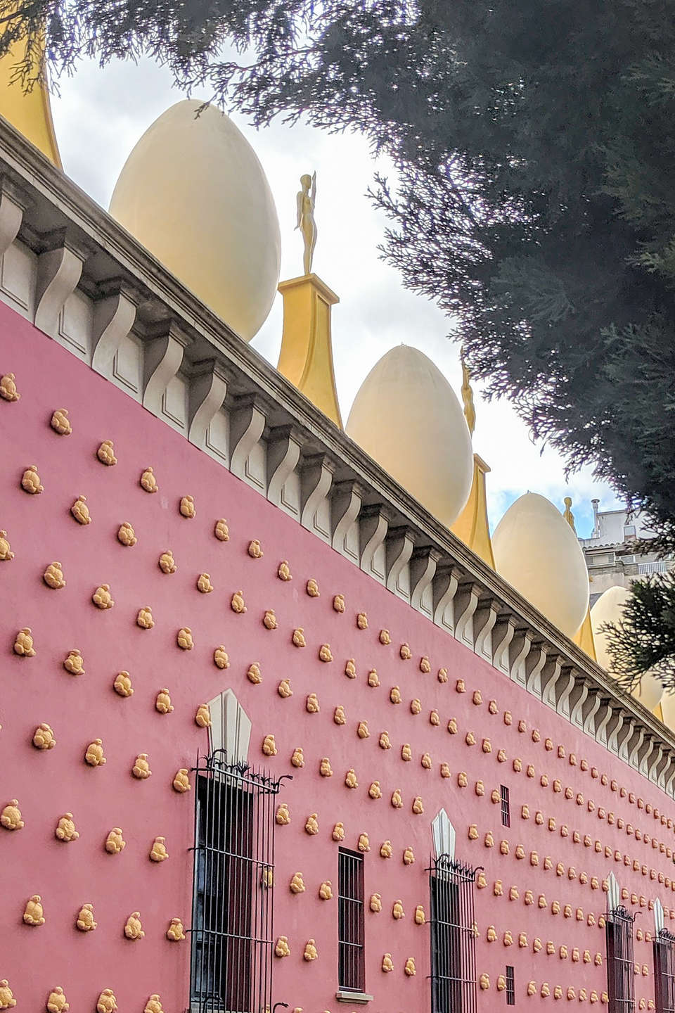 Exterior of the Salvador Dali Museum studded with plaster-covered croissants, and a roof topped with giant eggs and Oscars