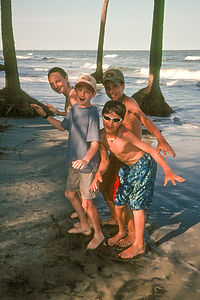 """Kids """"skim boarding"""" under palmetttos"""
